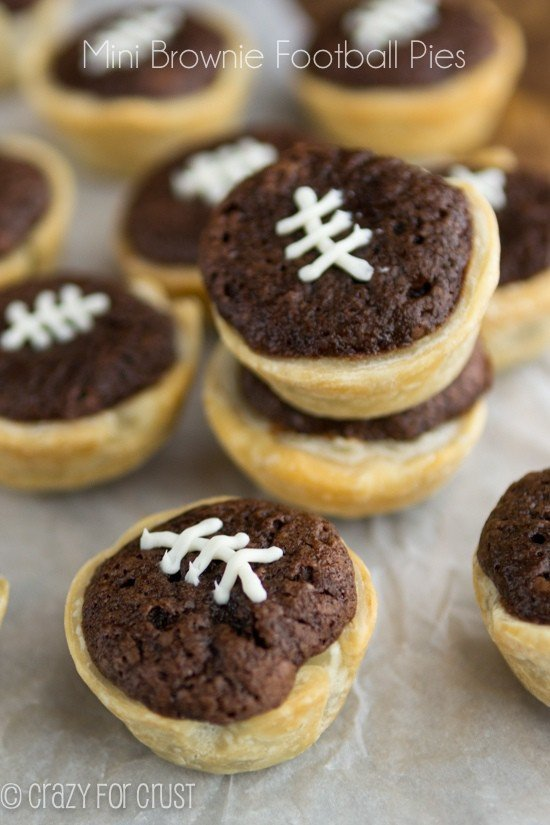 Mini brownie football pies on parchment paper with title