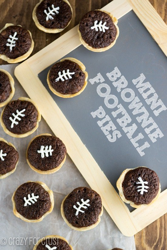 Overhead shot of mini brownie football pies on wood table with a chalkboard
