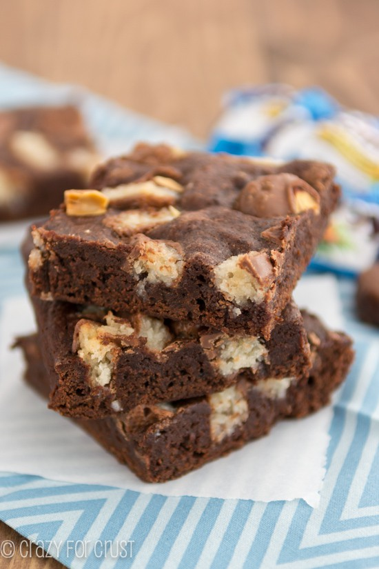 Stack of one bowl candy bar brownies with almond joy on parchment paper