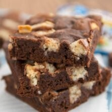 Stack of one bowl candy bar brownies on parchment paper with title