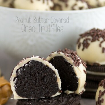 oreo truffle cut in half coated in peanut butter white chocolate with bowl of truffles behind