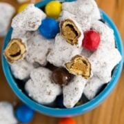 muddy buddies made with peanut butter pretzels and M&Ms in a blue dish