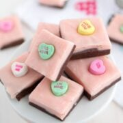 stack of valentine fudge with chocolate and pink layer and conversation hearts on white plate