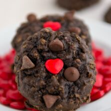 chocolate oatmeal cookie with red heart sprinkle on white plate with more sprinkles