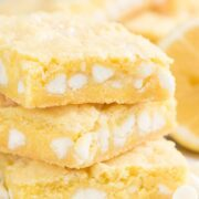Lemon gooey bar stack on parchment paper with title