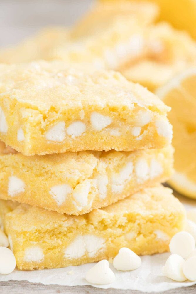 Stack of gooey lemon bars on parchment paper