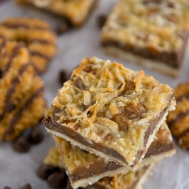 magic cookie bars in a stack with chocolate center and coconut caramel top