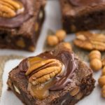 brownie with caramel and chocolate and a pecan on top on parchment paper