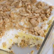 no bake lemon dessert in glass pan with slice missing