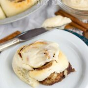 cinnamon roll on white plate with knife
