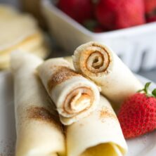 Cinnamon sugar pancake rolls on a white plate with a strawberry and more strawberries in background