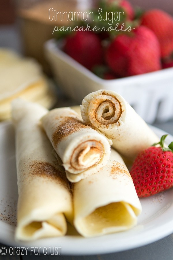 Cinnamon Sugar Pancake Rolls sitting on a white plate with a strawberry