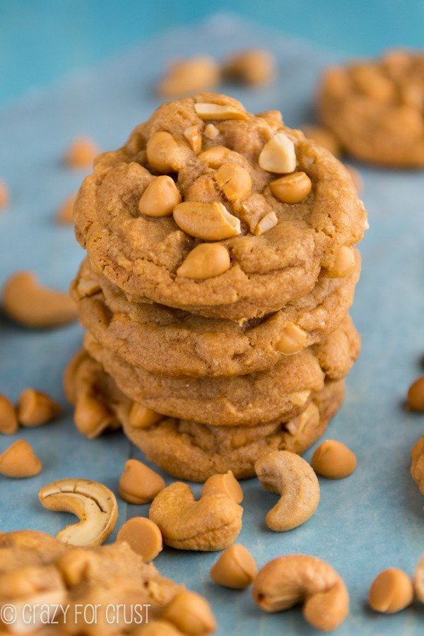 Butterscotch Pudding Cookies stacked on a blue towel with cashews all around the cookies