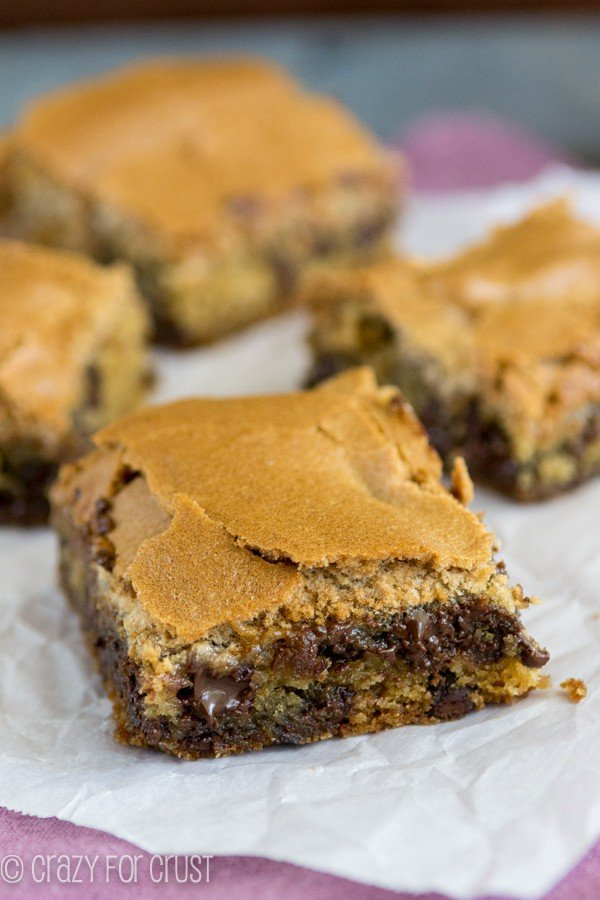 Chocolate Chip Cookie Mud Hen Bars - melty chocolate chip cookie topped with a brown sugar meringue sitting on parchment paper