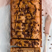 Healthier Banana Bread sitting on parchment paper with knife next to it
