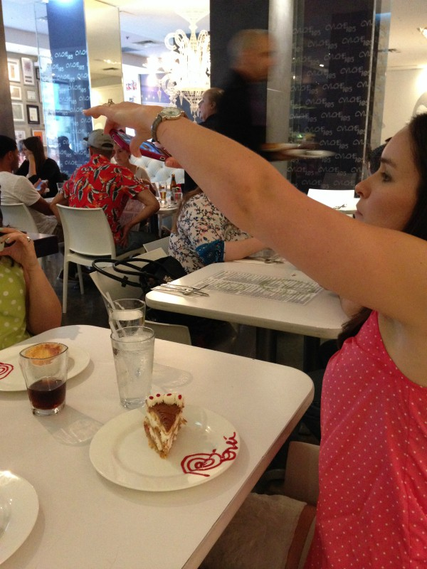 A girl taking a picture of her slice of cake in a restaurant