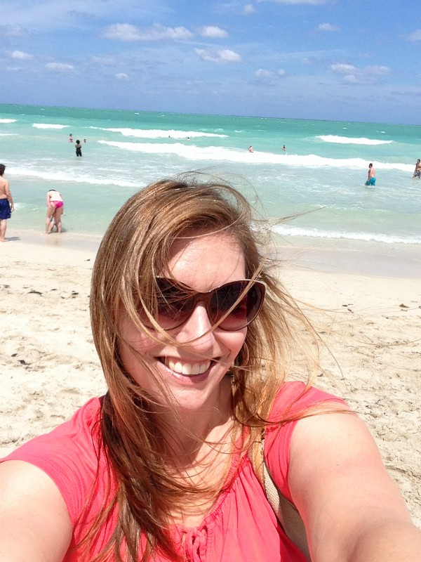 Girl In pink shirt wearing sunglasses and brown hair blowing in her face, standing in front of the ocean