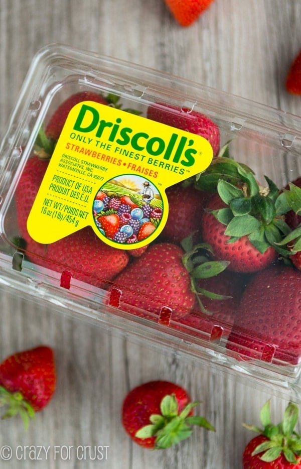 box of strawberries on a wooden board