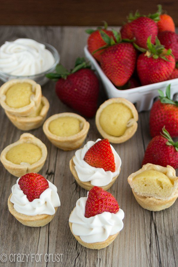 Mini Strawberry Shortcake Pies spread out with strawberries on a wooden board