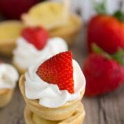Mini Strawberry Shortcake Pies stacked on top of each other with strawberries in the background