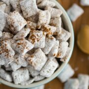 Peanut Butter Snickerdoodle Muddy Buddies sitting in a bowl and all over the table with spoonful of peanut butter laying there