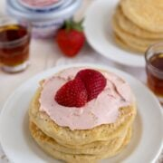 Strawberry Cheesecake Pancakes on a white plate with strawberries on top