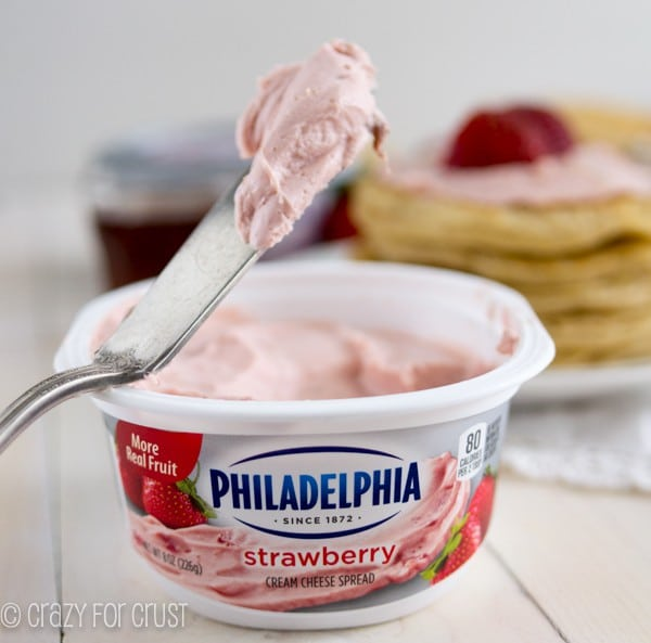 a knife scooping strawberry cream cheese out of the container
