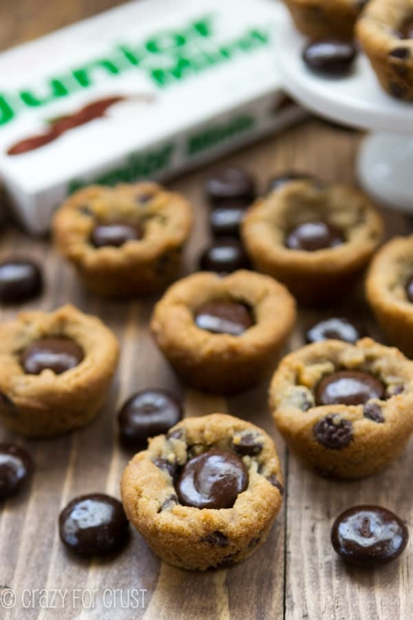 Junior Mint Chocolate Chip Cookie Cups on a wooden board with junior mint box in the background