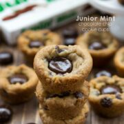 Junior mint chocolate chip cookie cups stacked on top of each other with junior mint box in the background