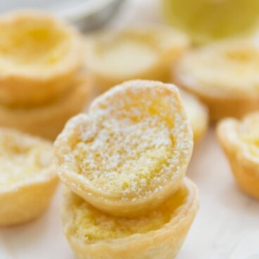 Mini Lemon Chess Pies stacked on top of each other with lemons in the background
