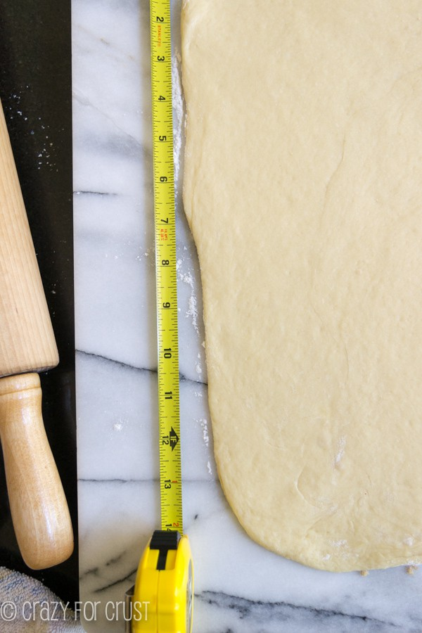 Overnight Cinnamon Rolls dough rolled out with a measuring tape along the side of the dough