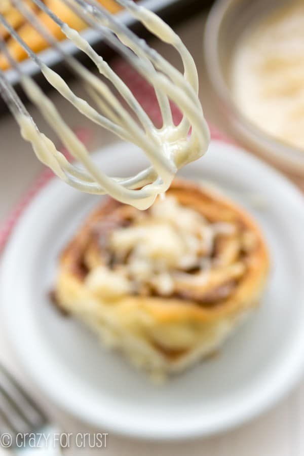 Perfect Overnight Cinnamon Rolls on a white plate with a mixer above it
