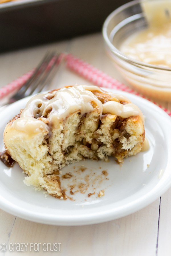 overnight cinnamon rolls on a white plate with a bite taken out of it