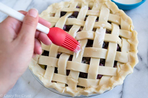 topping a lattice pie with cream