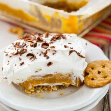 slice of pumpkin dessert on white plates with whipped cream and chocolate shavings