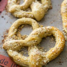 soft pretzel with almond topping on cookie sheet