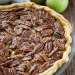 apple pecan pie with apples behind