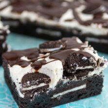 brownie on teal napkin with frosting and oreos