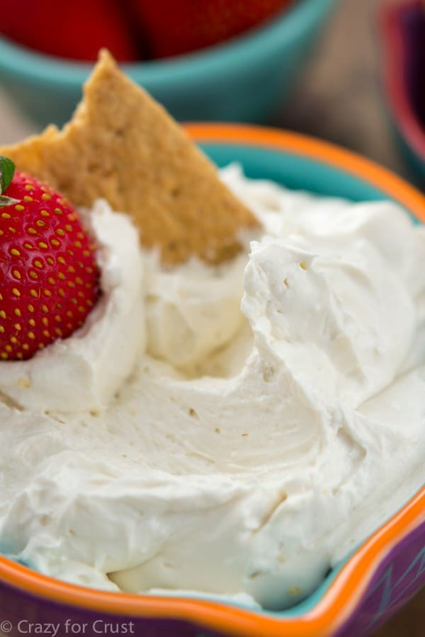 Skinny cheesecake dip with a strawberry and cracker being dipped.