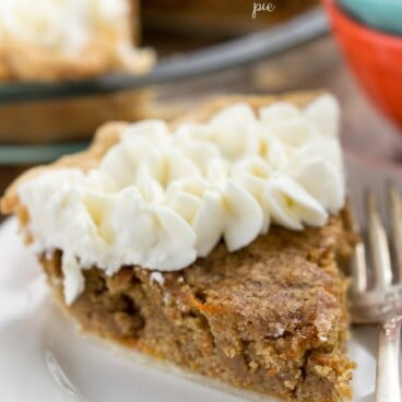 slice of carrot cake pie with whipped cream on white plate and fork