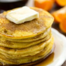 stack of orange pancakes on white plate