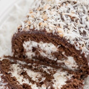 sliced chocolate coconut cake roll on plate