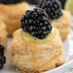 Close up shot of blackberry key lime tarts on a white plate with napkin underneath