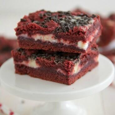 Red Velvet Gooey Bars on a white cake stand