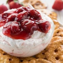 Strawberry Pretzel Salad Dip in a small glass bowl sitting on pretzels