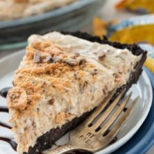 Slice of butterfinger ice cream pie on a white plate with chocolate drizzle