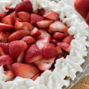 Close up shot of no bake strawberry shortcake pie with vanilla oreos and strawberries on the table