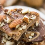 Peanut butter almond roca pieces on white plate