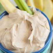 Skinny peanut butter dip in small blue bowl with celery