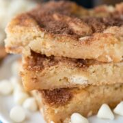 Stack of white chocolate snickerdoodle gooey bars on white plate